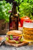 新鲜的自创汉堡和冰镇啤酒 免版税库存照片