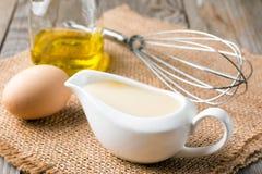 新鲜的自创白汁蛋黄酱和成份鸡蛋,在木背景的柠檬橄榄油 库存图片