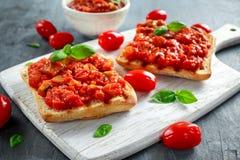新鲜的自创酥脆意大利开胃菜Bruschetta冠上了用蕃茄,茄子,夏南瓜,黄色胡椒,大蒜和 图库摄影
