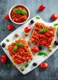 新鲜的自创酥脆意大利开胃菜Bruschetta冠上了用蕃茄,茄子,夏南瓜,黄色胡椒,大蒜和 免版税库存图片