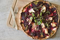 新鲜的自创馅饼用希腊白软干酪和甜菜根,在一把木板和葡萄酒白色背景、葡萄酒叉子和刀子 Copyspa 图库摄影