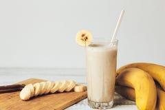 新鲜的自创香蕉圆滑的人、切板和香蕉在白色土气木头 免版税图库摄影