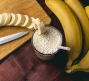 新鲜的自创香蕉圆滑的人、切板和香蕉在黑暗的土气木头 免版税库存图片