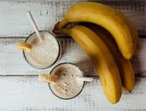 新鲜的自创香蕉圆滑的人和香蕉在白色土气木桌上,健康 免版税图库摄影