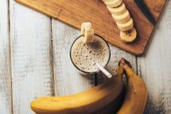 新鲜的自创香蕉圆滑的人和香蕉在白色土气木桌上,健康 库存照片
