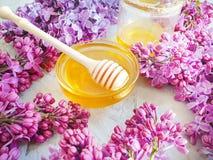 新鲜的自然甜蜂蜜淡紫色开花构成花营养可口在灰色具体背景 库存图片