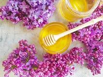 新鲜的自然甜蜂蜜淡紫色开花桌构成花营养可口在灰色具体背景 免版税库存照片