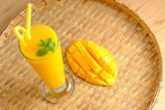 新鲜的芒果汁圆滑的人和芒果结果实与竹篮子 库存照片