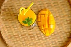 新鲜的芒果汁圆滑的人和芒果结果实与竹篮子 库存图片
