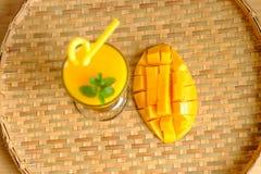 新鲜的芒果汁圆滑的人和芒果结果实与竹篮子 免版税库存照片
