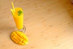 新鲜的芒果汁圆滑的人和芒果结果实与竹篮子 免版税库存图片