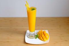 新鲜的芒果汁圆滑的人和芒果结果实与竹篮子 图库摄影