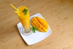 新鲜的芒果汁圆滑的人和芒果结果实与竹篮子 免版税图库摄影