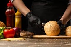 新鲜的芝麻小圆面包为汉堡做准备烹调,与在背景的成份的厨师,餐馆业,便当,鲜美食物 免版税图库摄影