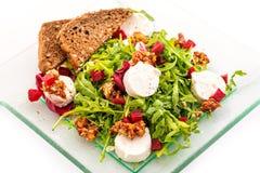 新鲜的芝麻菜沙拉用甜菜根、山羊乳干酪、面包切片和核桃在白色背景隔绝的玻璃板,产品phot 免版税库存图片