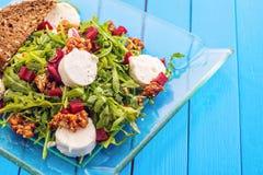 新鲜的芝麻菜沙拉用甜菜根、山羊乳干酪、面包切片和核桃在玻璃板在蓝色木背景,产品photogr 库存图片