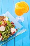 新鲜的芝麻菜沙拉用甜菜根、山羊乳干酪、面包切片和核桃在玻璃板在蓝色木背景,产品photogr 免版税库存照片