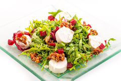 新鲜的芝麻菜沙拉用甜菜根、山羊乳干酪和核桃在白色背景隔绝的玻璃板,产品摄影稀土的 图库摄影