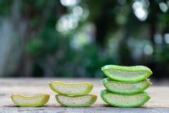 新鲜的芦荟维拉词根切片和胶凝体在木桌,皮肤疗法概念上 免版税库存图片