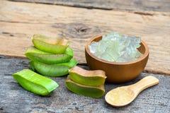 新鲜的芦荟维拉词根切片和胶凝体在木桌,皮肤疗法概念上 免版税库存照片