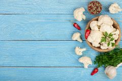 新鲜的花椰菜用大蒜和辣椒在蓝色木背景与拷贝空间您的文本的 顶视图 免版税库存照片