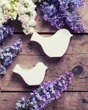 新鲜的芳香淡紫色花和两只装饰鸟在vintag 库存照片