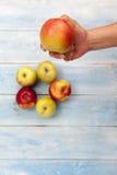 新鲜的苹果在手中和在蓝色木桌上 免版税库存照片