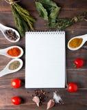 新鲜的草本、香料和笔记本在木桌上 免版税图库摄影