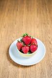 新鲜的草莓和汁液在木桌上 平的位置 库存图片