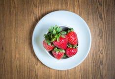 新鲜的草莓和汁液在木桌上 平的位置 免版税图库摄影
