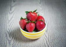 新鲜的草莓和汁液在木桌上 平的位置 图库摄影