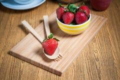 新鲜的草莓和汁液在木桌上 平的位置 库存照片