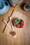 新鲜的草莓和汁液在木桌上 平的位置 免版税库存照片