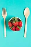 新鲜的草莓和汁液在蓝色背景 平的位置 库存照片