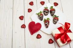 新鲜的草莓在黑暗的巧克力、礼物和心脏浸洗了在木背景 日s华伦泰 图库摄影