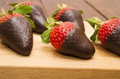 新鲜的草莓在黑暗的巧克力和心脏浸洗了在木背景 日s华伦泰 宏指令 图库摄影
