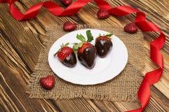 新鲜的草莓在黑暗的巧克力和心脏浸洗了在木背景 日s华伦泰 图库摄影