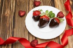 新鲜的草莓在黑暗的巧克力和心脏浸洗了在木背景 日s华伦泰 库存图片