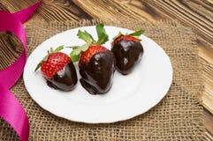 新鲜的草莓在黑暗的巧克力和心脏浸洗了在木背景 日s华伦泰 库存照片