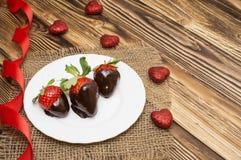 新鲜的草莓在黑暗的巧克力和心脏浸洗了在木背景 被限制的日重点例证s二华伦泰向量 免版税图库摄影