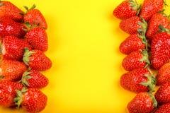 新鲜的草莓在黄色背景 图库摄影
