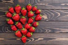 新鲜的草莓排列在老木背景的心脏形状 免版税图库摄影
