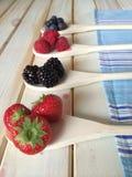 新鲜的草莓蓝莓和莓在减速火箭的厨房用桌背景 免版税库存照片