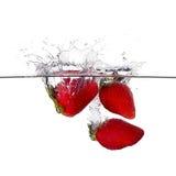 新鲜的草莓飞溅在白色背景隔绝的水中 免版税库存照片