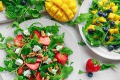 新鲜的草莓,芒果, blueberrie沙拉用希腊白软干酪,在白色板材的芝麻菜 图库摄影
