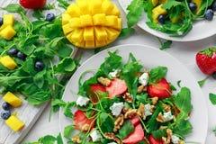 新鲜的草莓,芒果, blueberrie沙拉用希腊白软干酪,在白色板材的芝麻菜 免版税库存图片