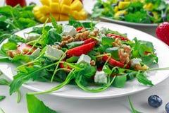 新鲜的草莓,芒果, blueberrie沙拉用希腊白软干酪,在白色板材的芝麻菜 免版税图库摄影