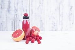 新鲜的莓、桃子、葡萄柚和汁液在塑料瓶 戒毒所 奶油被装载的饼干 复制空间 库存照片