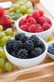 新鲜的莓果和绿色葡萄在一个木盘子,垂直 免版税库存照片