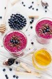 新鲜的莓果圆滑的人,奶昔,酸奶,装饰的点心磨碎了巧克力、蜂蜜和蓝莓 免版税库存图片